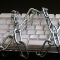 Image depicting an Apple keyboard wrapped up in links of chain